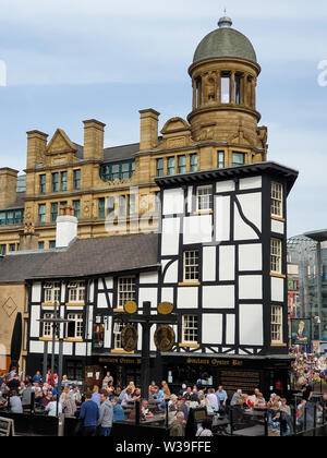 Manchester, United Kingdom - April 23, 2019: People enjoy themselves seated outsideat a pub in Manchster city centre on a beautuful spring afternoon - Stock Photo