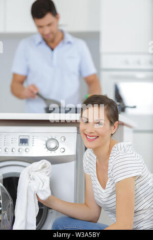 smiling woman taking cloths from washing machine - Stock Photo