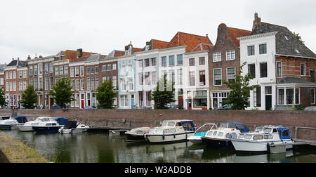 A canal in the city center of Middelburg with several boats and historical houses. - Stock Photo