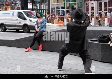 a photographer in a zoot suit and fedora takes a photo of a beautiful Asian woman with green hair. In Times Square, Manhattan, New York City - Stock Photo