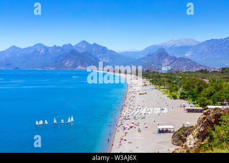 Panorama of a wide and long beach against the backdrop of mountains. Sea coast and a large beach. Blue sea with sailboats and a picturesque beach. Hol - Stock Photo