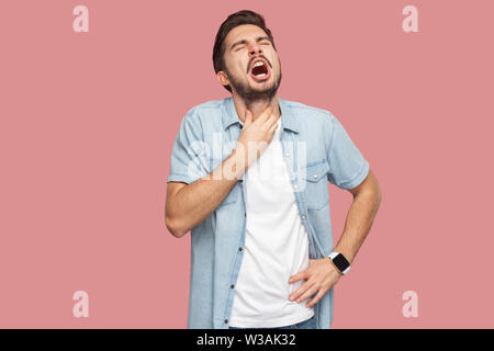 Throat pain or cold flu. Portrait of sad sick handsome bearded young man in blue casual style shirt standing and holding his painful neck and screamin - Stock Photo