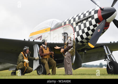 Re-enactors from Angels on our Wings, a Second World War re-enactment group, stand by TF-51D Mustang 'Contrary Mary' during the Flying Legends Air Show at IWM Duxford. - Stock Photo