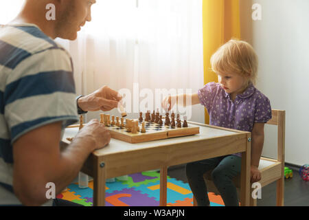 brain games - father teaches to play chess for his child at home