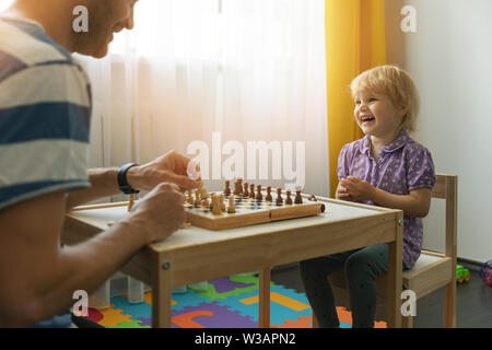 father and daughter having fun together learning to play chess at home - Stock Photo