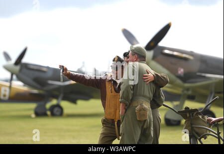 Re-enactors in Second World War dress take a selfie in front of Supermarine Spitfire's during the Flying Legends Air Show at IWM Duxford. - Stock Photo