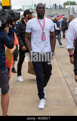 Silverstone, UK. 14th July, 2019.  FIA F1 Grand Prix of Britain, Race Day; Rapper Stormzy walking through the paddock Credit: Action Plus Sports Images/Alamy Live News - Stock Photo