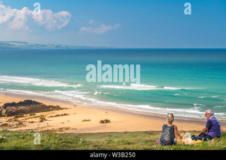 Cornwall, UK. 14th July, 2019. UK Weather. A couple enjoy the panoramic views over the North Cornish coast as the warm sunshine encourages tourists to visit the expansive beaches in Bude, North Cornwall. Credit: Terry Mathews/Alamy Live News - Stock Photo