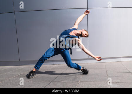 Young man dancing on street with arms outstretched - Stock Photo