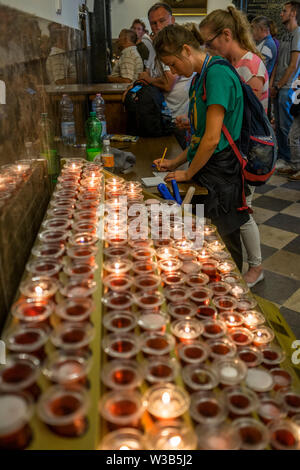 Inside the chapel where the icon of the Black Madonna of Czestochowa is shown, people ignite a candle to symbolize their prayer and write their intent - Stock Photo