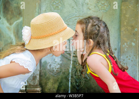 children drink water from a spring in Borjomi, Georgia. Selective focus. - Stock Photo