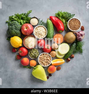 Healthy Vegan Food Background - organic food in heart shaped flat lay, top view. Healthy clean eating, diet  or detox concept. - Stock Photo