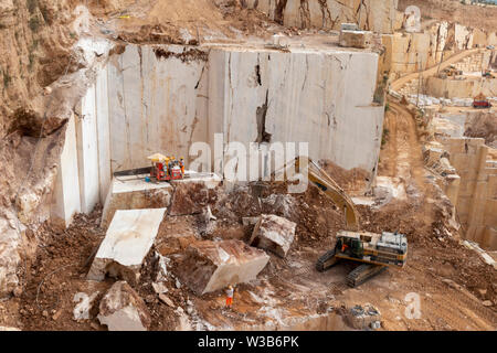 OROSEI, ITALY - June 14, 2019: Excavator works in a quarry, moving large slabs of marble. - Stock Photo