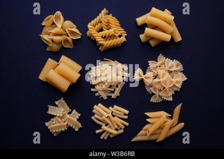 Various types of traditional Italian pasta isolated on black background from a high angle view - Stock Photo
