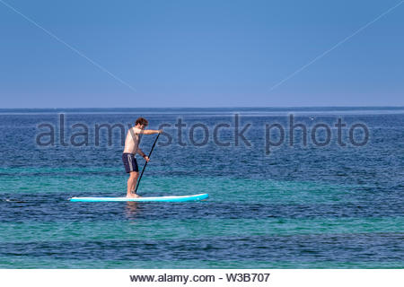 Alghero, Italy - 06.13.2019: Young caucasian male stands and paddles on stand-up paddle board. Sea and blue sky background. - Stock Photo