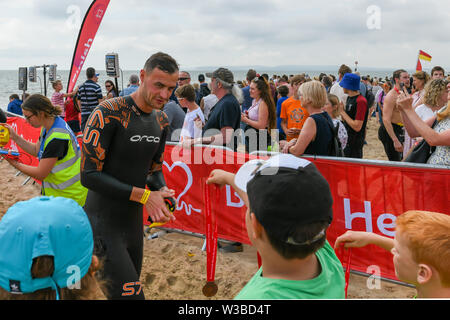 Bournemouth, UK. 14th July 2019. Hundreds of swimmers took to the water for the Bournemouth Pier to Boscombe Pier swim challenge. 2019 marks the 29th anniversary of the event, in aid of the British Heart Foundation. - Stock Photo