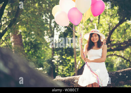 celebration and lifestyle concept - beautiful woman with colorful balloons outdoor in the park - Stock Photo