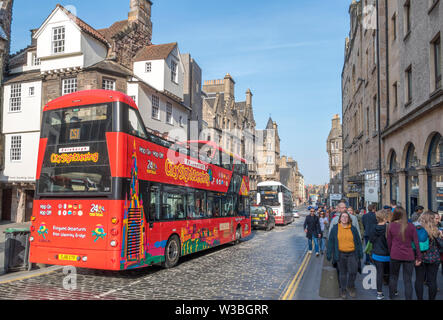 Open top city sightseeing bus on sunny High Street, with beautiful period architecture and people walking on the pavements. Edinburgh, Scotland, UK. - Stock Photo
