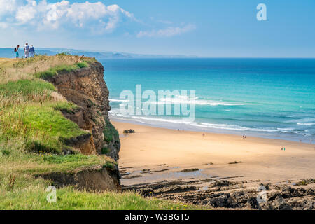 Bude Crooklets Beach, North Cornwall, England. Sunday 14th July 2019. UK Weather. People enjoy the panoramic views over the North Cornish coast as the warm sunshine encourages tourists to visit the expansive beaches in Bude, North Cornwall. - Stock Photo