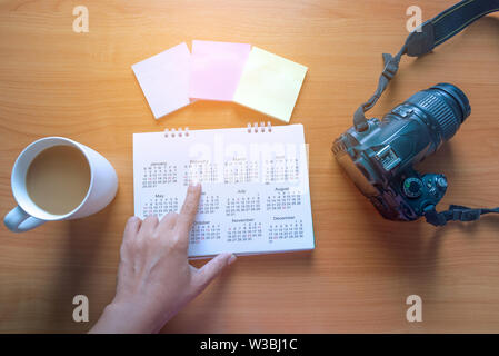 Travel Planning on Calendar and use post-it for note with a cup of coffee on a wooden table - Stock Photo