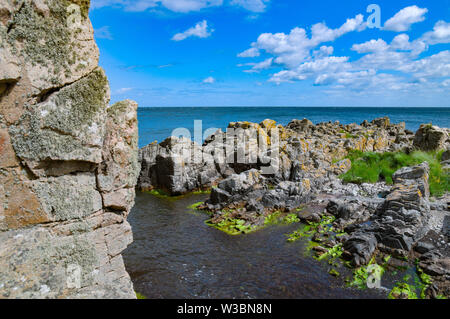 02 July 2019, Denmark, Gudhjem: Rugged rocks on the north coast of the Danish Baltic Sea island of Bornholm near the port of Gudhjem.  The island Bornholm is, together with the offshore archipelago Ertholmene, Denmark's most eastern island. Thanks to its location, the island of Bornholm counts many hours of sunshine. Photo: Patrick Pleul/dpa-Zentralbild/ZB - Stock Photo