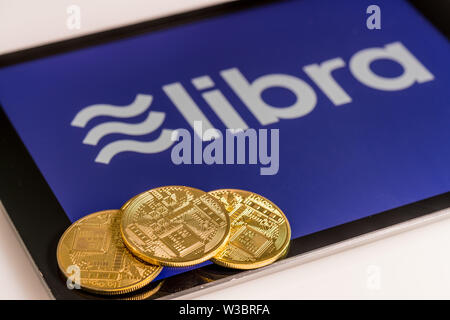 Golden coins on top of tablet computer for Libra cybercurrency - Stock Photo