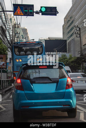 Cars stand at semaphore lights in the city streets. Traffic in downtown Bangkok, Thailand. - Stock Photo