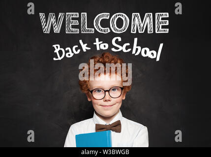 Cute little boy in glasses against chalkboard background. Back to school concept - Stock Photo