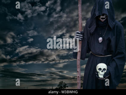 Grim reaper holds a skull in his hand, on a dark night sky. - Stock Photo