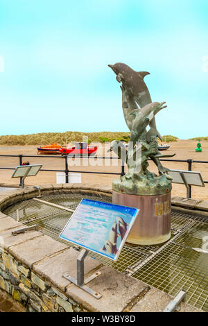 Statue of Cardigan Bay dolphins on the quayside in Barmouth, Gwynedd, Wales, UK - Stock Photo