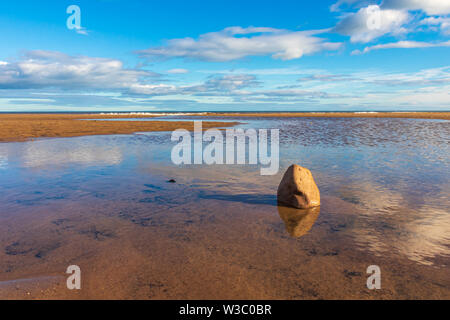 Rock in a pool of water on a sunny summers day on Fraisthorpe beachin North Yorkshire with the sea in the distance - Stock Photo