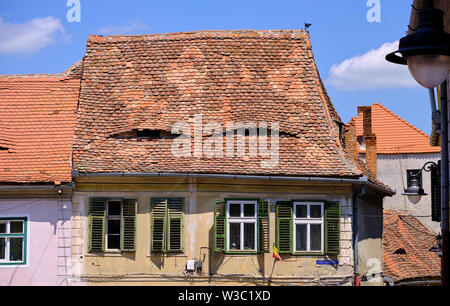 Typical Romanian roof top with lucarnes appearing like eye on the roof - Stock Photo