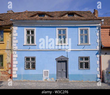 Typical Sibiu blue facade house with roof top with lucarnes appearing like eyes on the roof - Stock Photo