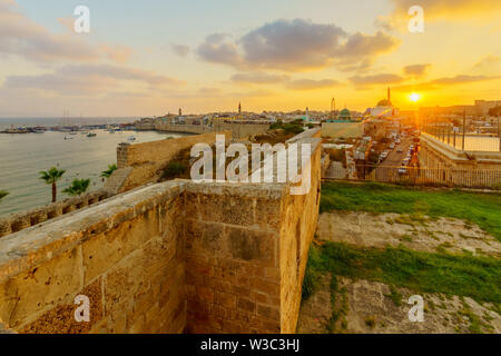 Sunset view with skyline, walls and fishing port, in the old city of Acre (Akko), Israel - Stock Photo