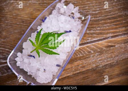 Cannabis infused soaking salts and marijuana leaf - cannabis spa concept - Stock Photo