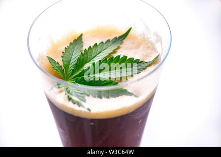 Detail of cold glass of beer with cannabis leaf  isolated over white, marijuana infused beverage concept - Stock Photo