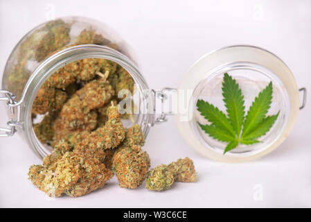 Detail of cannabis buds on clear glass jar isolated on white - medical marijuana dispensary concept - Stock Photo