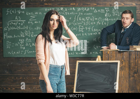 Young female student in pink cardigan and blue jeans standing in front of green board. Brunette teenage girl in the classroom listening to - Stock Photo