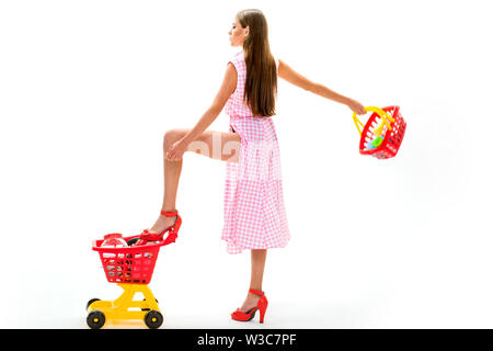 retro woman go shopping. vintage housewife woman isolated on white. woman going to make payment in supermarket. shopping girl with full cart. savings - Stock Photo