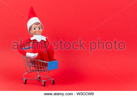 Christmas toy elf on shelf sitting in mini shopping cart on red background - Stock Photo