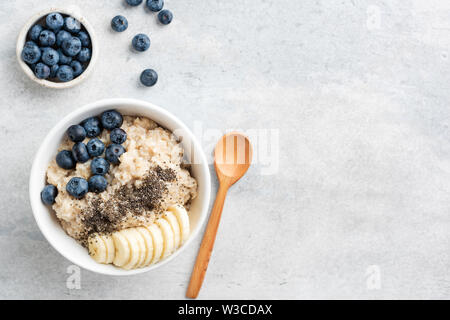 Healthy Breakfast Oatmeal Bowl With Banana, Blueberry And Chia Seeds In Bowl On Grey Concrete Background. Top View Copy Space - Stock Photo