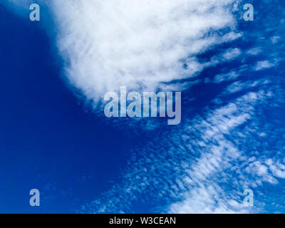 Cirrocumulus clouds are small rounded puffs that usually appear in long rows high in the sky. Cirrocumulus are usually white, but sometimes appear gra - Stock Photo