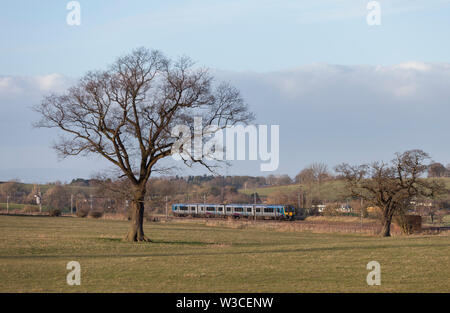 First Transpennine Express class 350 elcectric train passing Brisco (South of Carlisle) on the WCML with a Glasgow Central - Manchester Airport train - Stock Photo