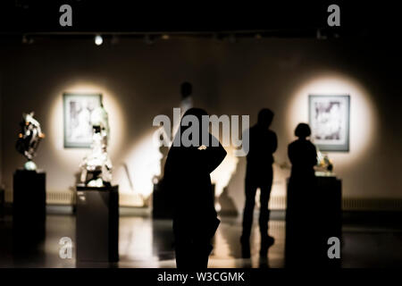 Silhouettes of unrecognizable people, visitors to an art gallery, a museum with paintings, selective focus - Stock Photo