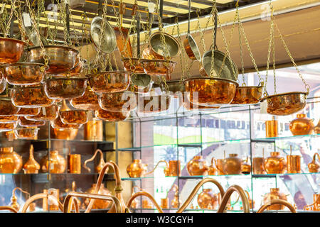 Copper ware, serpentine and jugs on the shop window in the store. - Stock Photo