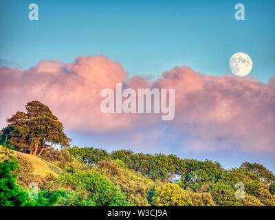 Weather UK: Nearly full moon rising over Wirksworth, Derbyshire, UK. HRD Image 14/7/2019 - Stock Photo