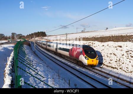 Virgin trains class 390 pendolino train passing Hardendale, Shap on the west coast mainline in Cumbria rushing through the snow - Stock Photo