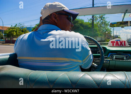 Varadero - Cuba / October 11 2011, Cuban taxi driver in his classic american convertible car takes tourists back to hotel - Stock Photo