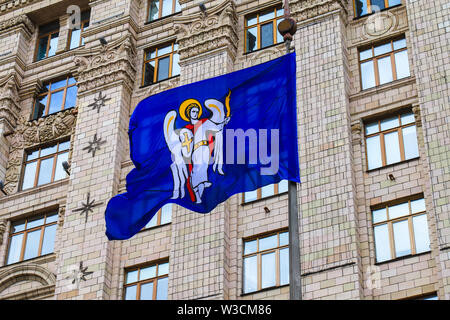 Blue flag of Kyiv, the capital of Ukraine, with a coat of arms against the background of the Kiev mayor s office building, city council, Kiev City - Stock Photo