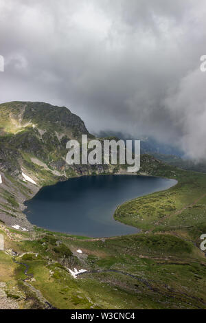 Misty, dramatic, moody view of famous Kidney lake on Rila mountain in Bulgaria and sunlit rocky highlands - Stock Photo